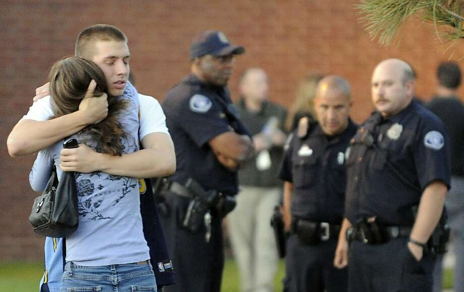 Witness Jacob Stevens, 18, hugs his mother Tammi after a police interview outside Gateway High School. Photo: RJ Sangosti, Associated Press
