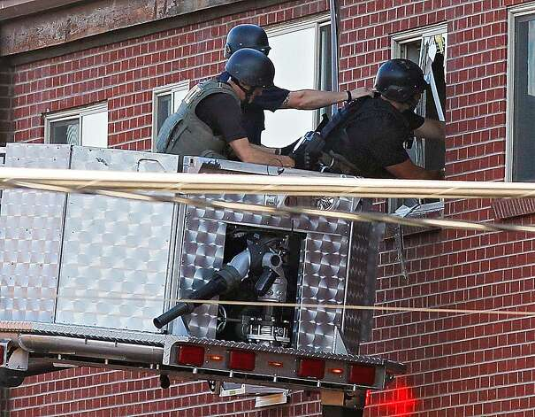 Police use a video camera to look inside an apartment  where the suspect in a shooting at a movie theatre lived in Aurora, Colo., Friday, July 20, 2012. As many as 12 people were killed and 50 injured at a shooting at the Century 16 movie theatre early Friday during the showing of the latest Batman movie. (AP Photo/Ed Andrieski) Photo: Ed Andrieski, Associated Press