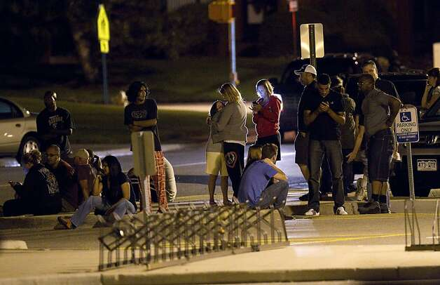 "Family and friends wait outside Gateway High School where witnesses were brought for questioning after a shooting at a movie theater showing the Batman movie ""The Dark Knight Rises,"" Friday, July 20, 2012 in Aurora, Colo.  A gunman wearing a gas mask set off an unknown gas and fired into the crowded movie theater killing 12 people and injuring at least 50 others, authorities said. (AP Photo/Barry Gutierrez) Photo: Barry Gutierrez, Associated Press"