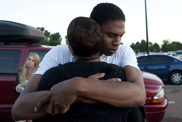 "Eyewitness Isaiah Bow hugs his mother Shamecca Davis after being questioned by police outside Gateway High School where witnesses were brought in, Friday, July 20, 2012 in Aurora, Colo.  After leaving the theater Bow went back in to find his girlfriend. ""I didn't want to leave her in there. But she's ok now,"" Bow said.   A gunman wearing a gas mask set off an unknown gas and fired into the crowded movie theater killing 12 people and injuring at least 50 others, authorities said. (AP Photo/Barry Gutierrez) Photo: Barry Gutierrez, Associated Press"