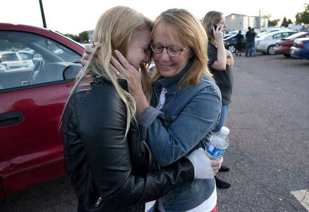 Emma Goos, 19, hugs her mother, Judy Goos, outside Gateway High School where witnesses were brought for questioning Friday, July 20, 2012, in Aurora, Colo. Emma was in the third row of the theater of the new Batman movie when the shooter entered. She helped apply pressure to a man's head who was injured. (AP Photo/Barry Gutierrez) Photo: Barry Gutierrez, Associated Press