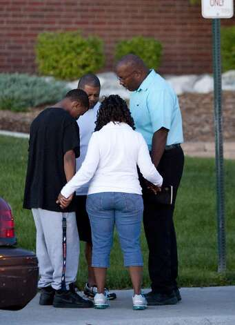 A small group prays outside Gateway High School where witness were brought for questioning Friday, July 20, 2012 in Aurora, Colo.  A gunman wearing a gas mask set off an unknown gas and fired into the crowded movie theater killing 12 people and injuring at least 50 others, authorities said. Photo: Barry Gutierrez, Associated Press