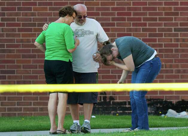 Tom Sullivan, center, stands with family members outside Gateway High School where witness were brought for questioning after a gunman opened fire at the midnight premiere of The Dark Knight Rises Batman movie Friday, July 20, 2012 in Aurora, Colo. Sullivan later pleaded with the media to help find his missing son, Alex Sullivan, who attended the movie to celebrate his 27th birthday.   A gunman wearing a gas mask set off an unknown gas and fired into the crowded movie theater killing 12 people and injuring at least 50 others, authorities said. (AP Photo/Barry Gutierrez) Photo: Barry Gutierrez, ASSOCIATED PRESS / The Associated Press2012
