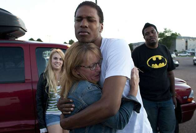 "Judy Goos, second from left, hugs her daughters friend,  Isaiah Bow, 20, while eye witnesses Emma Goos, 19, left, and Terrell Wallin, 20, right, gather outside Gateway High School where witness were brought for questioning Friday, July 20, 2012 in Denver.   A gunman wearing a gas mask set off an unknown gas and fired into a crowded movie theater at a midnight opening of the Batman movie ""The Dark Knight Rises,"" killing at least 12 people and injuring at least 50 others, authorities said. (AP Photo/Barry Gutierrez) Photo: Barry Gutierrez, Associated Press"