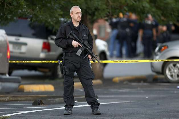 A SWAT team officer stands watch near an apartment house where the suspect in a shooting at a movie theatre lived in Aurora, Colo., Friday, July 20, 2012. As many as 14 people were killed and 50 injured at a shooting at the Century 16 movie theatre early Friday during the showing of the latest Batman movie. (AP Photo/Ed Andrieski) Photo: Ed Andrieski, Associated Press