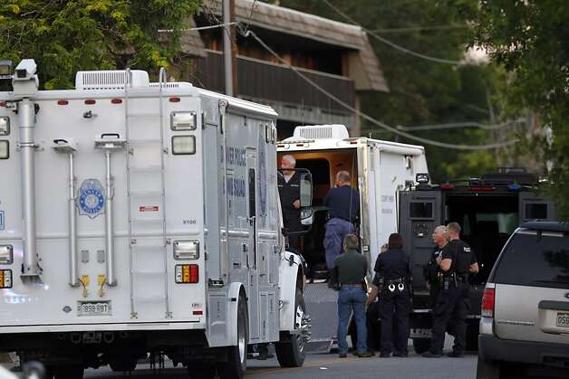 Police gather near an apartment house where the suspect in a shooting at a movie theatre lived in Aurora, Colo., Friday, July 20, 2012. As many as 14 people were killed and 50 injured at a shooting at the Century 16 movie theatre early Friday during the showing of the latest Batman movie. (AP Photo/Ed Andrieski) Photo: Ed Andrieski, Associated Press