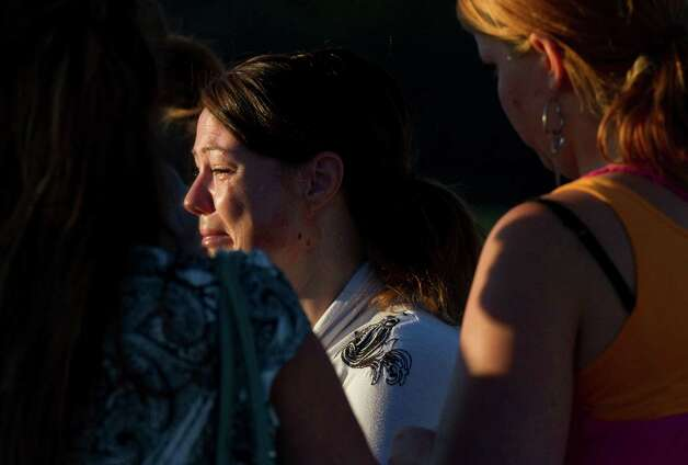 A woman cries outside Gateway High School where witness were brought for questioning after a gunman opened fire at a midnight premiere of The Dark Knight Rises Batman movie Friday, July 20, 2012 in Aurora, Colo. A gunman wearing a gas mask set off an unknown gas and fired into the crowded movie theater killing 12 people and injuring at least 50 others, authorities said.(AP Photo/Barry Gutierrez) Photo: Barry Gutierrez, ASSOCIATED PRESS / AP2012