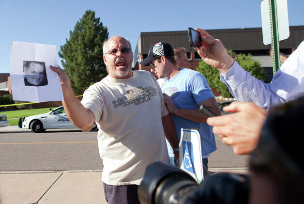 Tom Sullivan , holds a photograph of his son, Alex Sullivan, as he pleads with the media to help him find his son, outside Gateway High School on Friday, July 20, 2012 in Aurora, Colo.  Alex Sullivan, was celebrating his 27th birthday by attending midnight premiere of the Batman movie Friday night.  A gunman wearing a gas mask set off an unknown gas and fired into the crowded movie theater killing 12 people and injuring at least 50 others, authorities said. (AP Photo/Barry Gutierrez) Photo: Barry Gutierrez, ASSOCIATED PRESS / AP2012