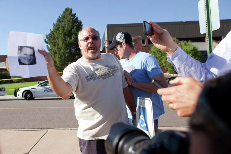 Tom Sullivan , holds a photograph of his son, Alex Sullivan, as he pleads with the media to help him