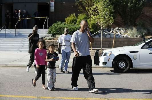 "Ian Legins of Aurora, Colorado and his two daughters, leave Gateway High School where families of the shooting victims and survivors are meeting to connect with their missing loved ones. Legins is on the phone after trying to get information on his nephew Gabriel Conely who was with some friends at the showing of ""The Dark Knight Rises"" at the Century 16 theater in Aurora, Colorado when a gunman opened fire on the audience, on July 20, 2012.  The shooting suspect in custody has been identified as 24-year-old James Holmes, US media said Friday. Television networks cited the FBI as saying that Holmes, from the town of Aurora, Colorado, scene of the midnight shooting at a screening of the Batman movie, did not appear to have any known terrorism connections. AFP PHOTO/JONATHAN CASTNERJONATHAN CASTNER/AFP/GettyImages Photo: Jonathan Castner, AFP/Getty Images"
