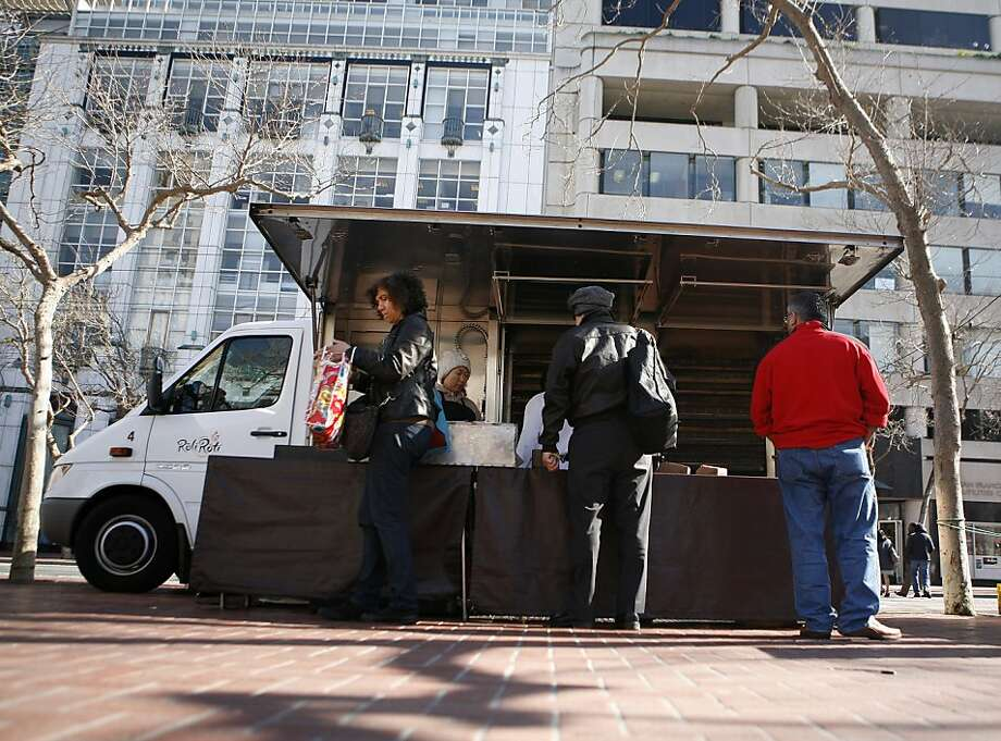 Customers buy roasted chicken from the Roli Roti food truck at the UN Plaza Farmer's Market on Wednesday, February 23, 2011. Photo: Anna Vignet, The Chronicle