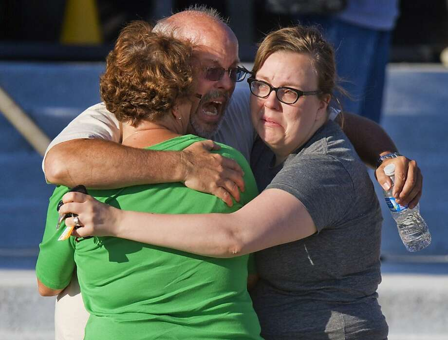 "Tom Sullivan, center, embraces family members outside Gateway High School where he has been searching franticly for his son Alex Sullivan who celebrated his 27th birthday by going to see ""The Dark Knight Rises,"" movie where a gunman opened fire Friday, July 20, 2012, in Aurora, Colo. (AP Photo/Barry Gutierrez) Photo: Barry Gutierrez, Associated Press"