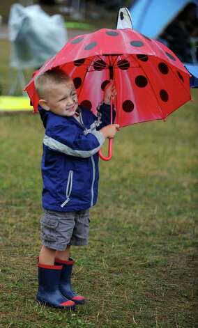 Three-year-old Landes Hough, of Providence, RI, takes cover under his lady bug umbrella during the Gathering of the Vibes at Seaside Park in Bridgeport, Conn. Friday, July 20, 2012. Photo: Autumn Driscoll / Connecticut Post freelance