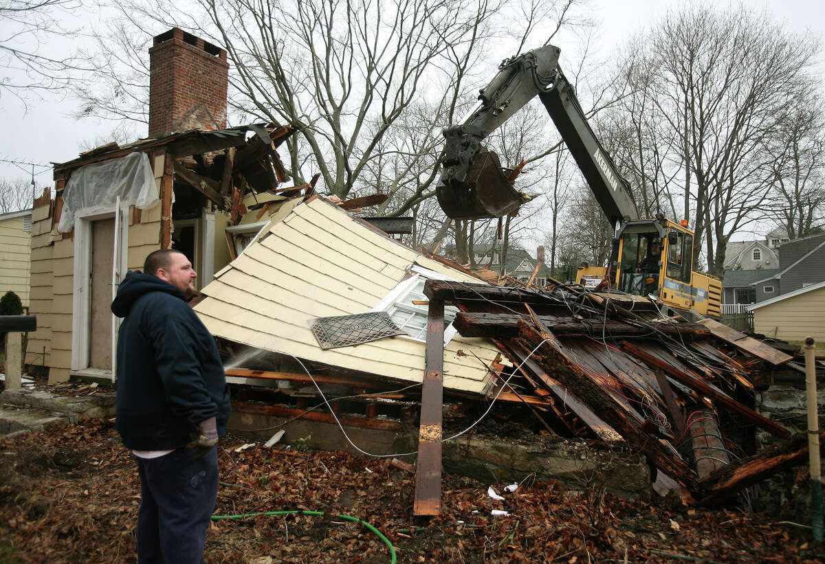 Michael Rodrigues, left, and his father Manuel Rodrigues, both of Bridgeport, of Manny's Excavating, demolish a house at 410 South Benson Road in Fairfield on Wednesday, February 8, 2012. The size of the new house under construction at the property on the corner of South Benson and Judson roads has become the topic of debate.