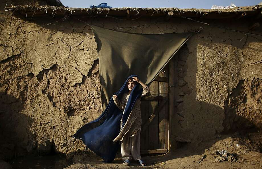 Afghan refugee Pasmeena Basheer, 6, holds on to her headscarf against the wind while standing in the doorway of a home in a slum area on the outskirts of Islamabad, Pakistan, Friday, July 20, 2012. (AP Photo/Muhammed Muheisen) Photo: Muhammed Muheisen, Associated Press