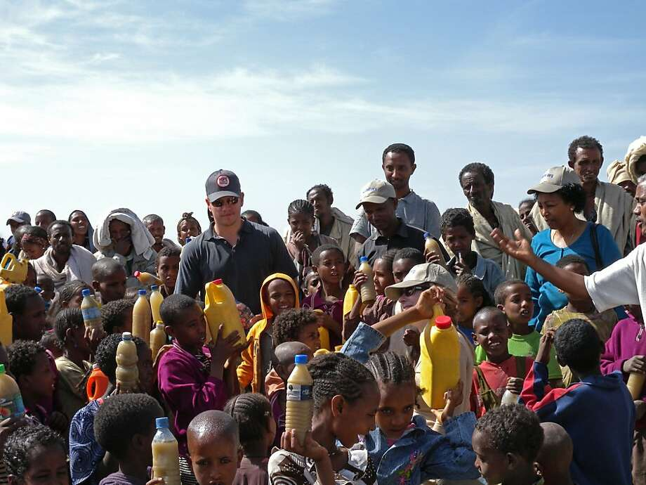 Matt Damon with children in Tigray, Ethiopia, holding the dirty water they will take with them to school. Photo: Water.org
