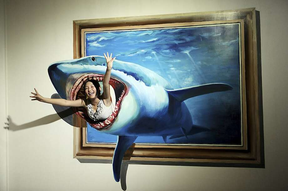 Devoured by art:A visitor poses with a 3D painting during a show in Hefei, China.  Photo: Associated Press