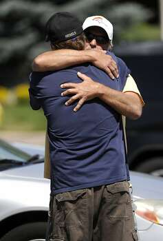 Two men hug outside Gateway High School in Aurora, Colo., where witnesses are being interviewed by authorities Friday, July 20, 2012. A  gunman wearing a gas mask set off an unknown gas and fired into the crowded movie theater killing 12 people and injuring dozens, authorities said.  The suspect is identified as 24-year-old James Holmes.(AP Photo/The Denver Post, Craig F. Walker) TV, INTERNET AND MAGAZINES CALL FOR RATES AND TERMS Photo: Craig F. Walker, Associated Press