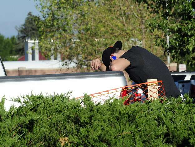 A man makes a call outside the University of Colorado Hospital on Friday, July, 19, 2012 in Aurora, Colo., Friday, July 20, 2012.  A gunman wearing a gas mask set off an unknown gas and fired into the crowded movie theater killing 12 people and injuring at least 50 others, authorities said.  (AP Photo/The Denver Post, Heather Rousseau) TV, INTERNET AND MAGAZINES CALL FOR RATES AND TERMS Photo: Heather Rousseau, Associated Press