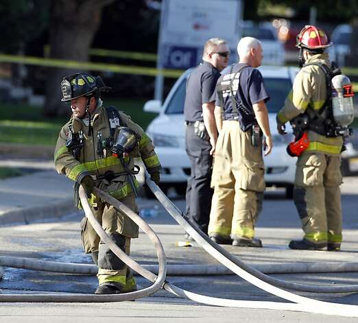 Firefighters work in front of an apartment where the suspect in a theatre shooting lived in Aurora, Colo., on Friday, July 20, 2012. As many as 12 people were killed and 50 injured at a shooting at the Century 16 movie theatre on Friday. The suspect is identified as 24-year-old James Holmes.  (AP Photo/Ed Andrieski) Photo: Ed Andrieski, Associated Press