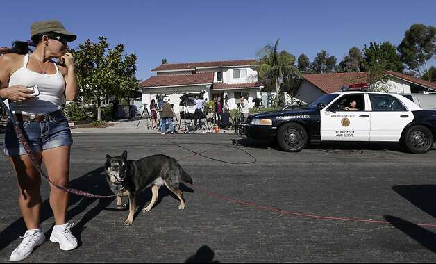 Julie Adams, left, walks her dog past police and reporters outside the home of the mother of Colorado shooting suspect, James Holmes, Friday, July 20, 2012, in San Diego. A gunman in a gas mask barged into a crowded Denver-area theater during a midnight showing of the Batman movie on Friday, hurled a gas canister and then opened fire in one of the deadliest mass shootings in recent U.S. history. (AP Photo/Gregory Bull) Photo: Gregory Bull, Associated Press