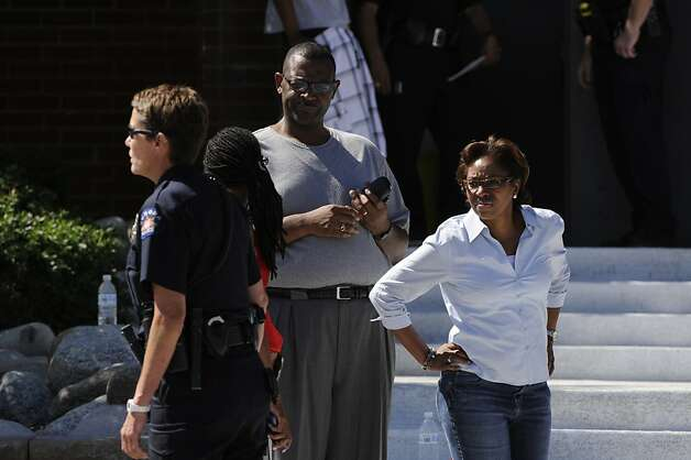 State Representative Rhonda Fields, left, arrives at Gateway High School in Aurora, Colo, where witnesses are being interviewed by authorities Friday, July 20, 2012. A gunman wearing a gas mask set off an unknown gas and fired into the crowded movie theater killing 12 people and injuring at least 50 others, authorities said.  The suspect is identified as 24-year-old James Holmes. (AP Photo/The Denver Post, Craig F. Walker) TV, INTERNET AND MAGAZINES CALL FOR RATES AND TERMS Photo: Craig F. Walker, Associated Press