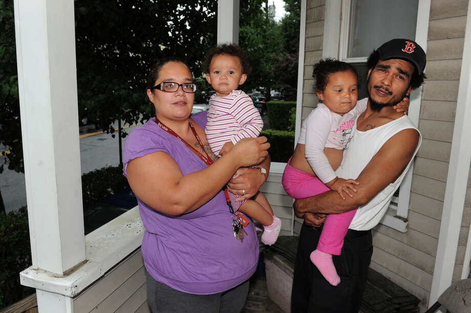 Ileana and Jose Cotto stand with their daughters, Leila and Joselyn, on the porch of their home on Austin Street, in Bridgeport, Conn. July 20th, 2012. Five blocks from Seaside Park, the Cottos say their street gets clogged with traffic from Gathering of the Vibes, and that they can hear the music late into the night. Photo: Ned Gerard / Connecticut Post