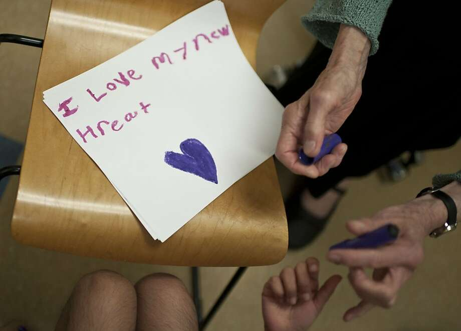 Lucile Packard Children's Hospital heart transplant social worker Mary Burge gives Abi Morgan-Mendoza crayons to make a picture to show how she's feeling. Photo: Yue Wu, The Chronicle