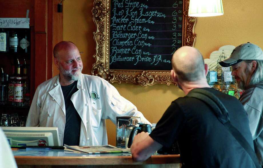 Leonard Meuse, left, briefly smiles while he serves customers at the newly re-opened Cafe Racer Friday, July 20, 2012, in Seattle. The cafe opened again Friday morning, seven weeks after the shooting that wounded Meuse and killed four other people there seven weeks earlier. After the shooting on May 30 at the cafe, gunman Ian Stawicki also killed a woman in a carjacking in Seattle before taking his own life. Photo: Ap