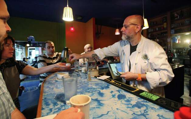 Leonard Meuse, right, serves customers at the newly re-opened Cafe Racer Friday, July 20, 2012, in Seattle. The cafe opened again Friday morning, seven weeks after the shooting that wounded Meuse and killed four other people there seven weeks earlier. After the shooting on May 30 at the cafe, gunman Ian Stawicki also killed a woman in a carjacking in Seattle before taking his own life. Photo: Ap