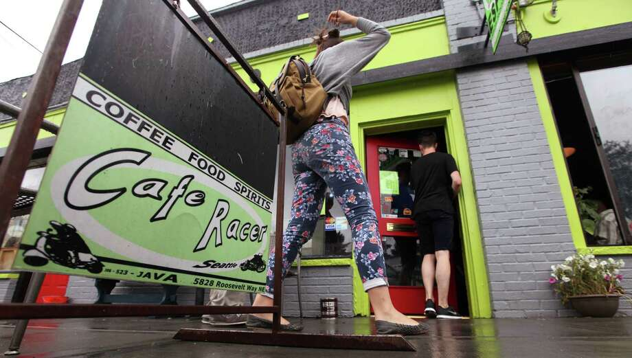 Patrons enter the newly re-opened Cafe Racer Friday, July 20, 2012, in Seattle. Photo: Ap