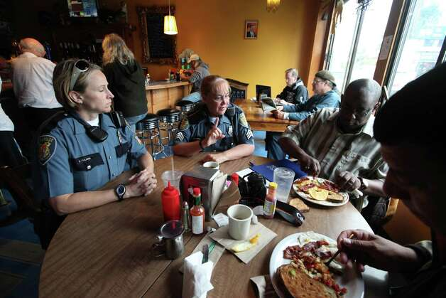 Police officers join patrons eating breakfast at the newly re-opened Cafe Racer Friday, July 20, 2012, in Seattle. The cafe opened again Friday morning, seven weeks after the shooting that wounded Leonard Meuse and killed four other people there seven weeks earlier. After the shooting on May 30 at the cafe, gunman Ian Stawicki also killed a woman in a carjacking in Seattle before taking his own life. Photo: Ap