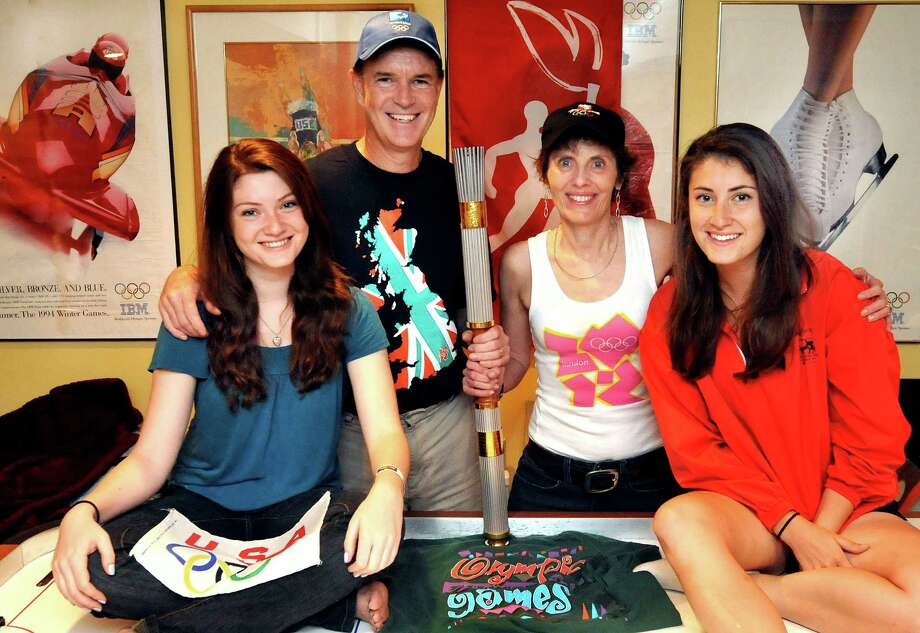 Jim Keller is going to his sixth Olympics and taking his family with him. The family is shown here with memoribilia in their New Fairfield home Friday, July 20, 2012. From left are daughter, Alyse; Keller, his wife, Denise; and daughter, Jana. Photo: Michael Duffy / The News-Times