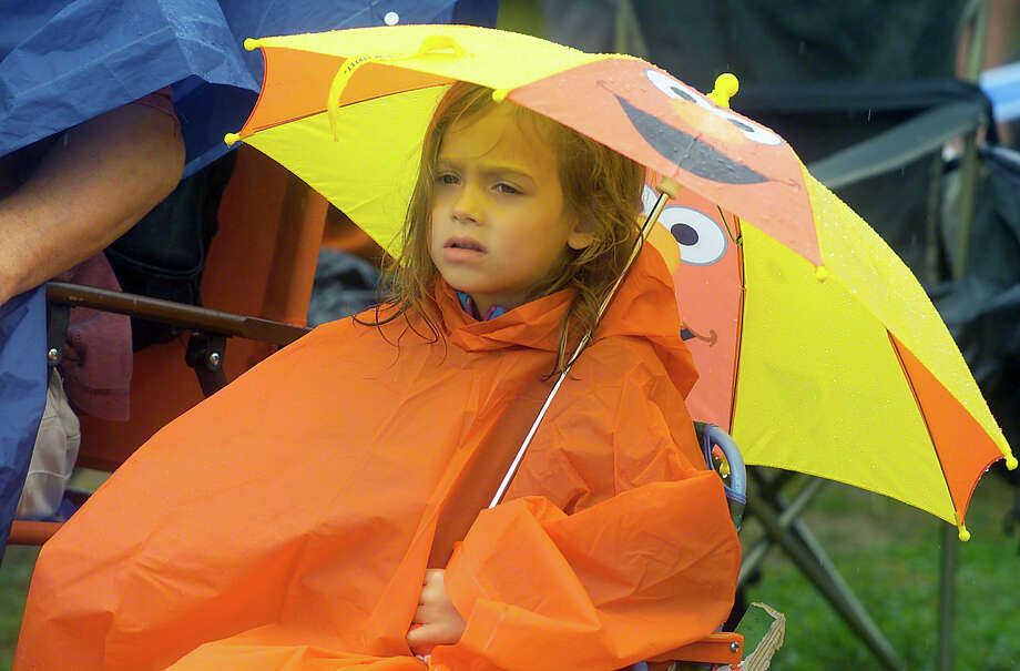 Natalia Grace-DuBack, of Torrington, covers up from the rain while at the Gathering of the Vibes concert at Seaside Park in Bridgeport, Conn. on Friday July 20, 2012. Photo: Christian Abraham / Connecticut Post freelance