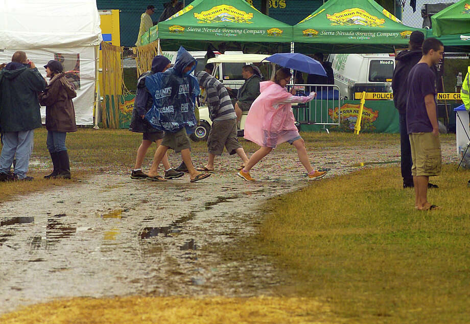 Concertgoers make their way through the mud at the Gathering of the Vibes concert at Seaside Park in Bridgeport, Conn. on Friday July 20, 2012. Photo: Christian Abraham / Connecticut Post freelance
