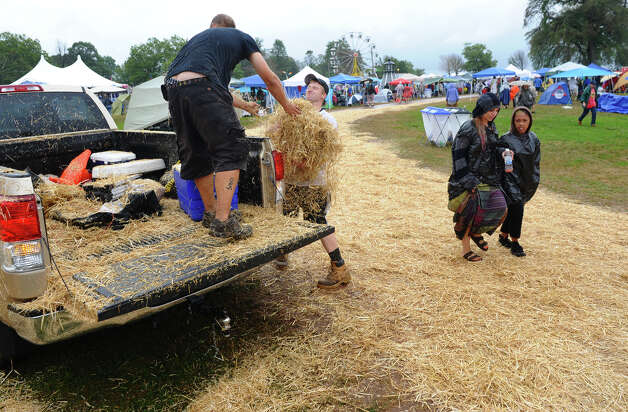 Vibes workers lay down hay in muddy areas at the Gathering of the Vibes concert at Seaside Park in Bridgeport, Conn. on Friday July 20, 2012. Photo: Christian Abraham / Connecticut Post freelance