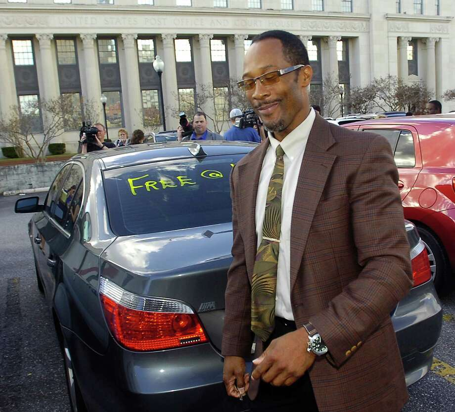 On Thursday, BISD trustees voted to renew electrician Calvin Walker's contract. In this photo after a mistrial in his federal trial, Calvin Walker smiles as he walks past a message on his rear windshield, and the media who had surrounded him and his wife, after leaving the Federal Courthouse.  Dave Ryan/The Enterprise