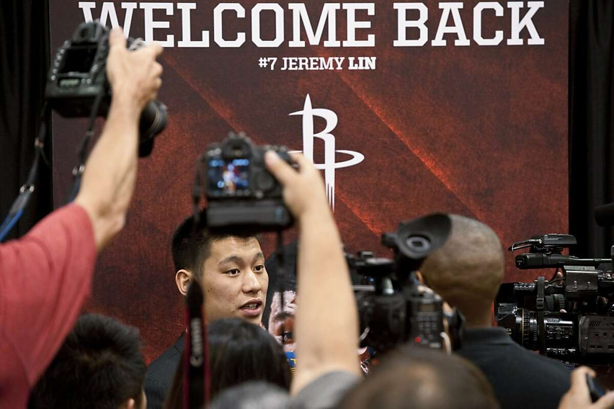 Jeremy Lin is the subject of attention after the Houston Rockets NBA basketball team held a news conference to re-introduce Lin, Thursday, July 19, 2012, in Houston. The 23-year-old Lin returned to Houston after signing a three-year, $25 million offer sheet that the New York Knicks decided not to match. (AP Photo/Dave Einsel)