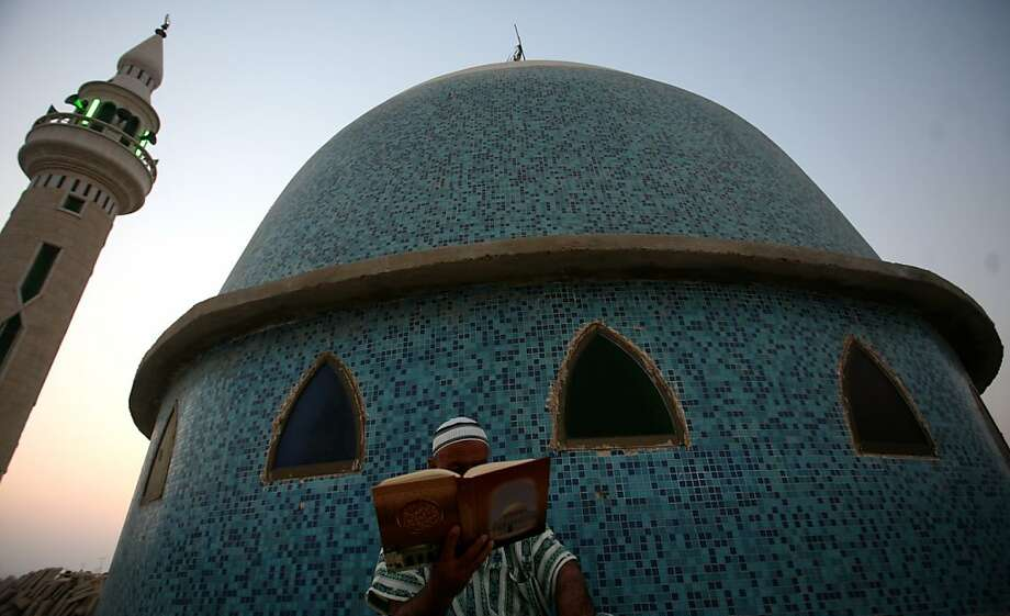 A Palestinian man reads the Koran outside a mosque in the West Bank city of Jenin on the first day of the Muslim holy fasting month of Ramadan on July 20, 2012.  AFP PHOTO / SAIF DAHLAHSAIF DAHLAH/AFP/GettyImages Photo: Saif Dahlah, AFP/Getty Images