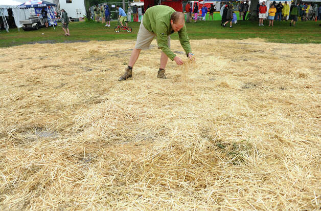 Vibes worker Matt Feicht spreads hay at the Gathering of the Vibes concert at Seaside Park in Bridgeport, Conn. on Friday July 20, 2012. Photo: Christian Abraham / Connecticut Post freelance