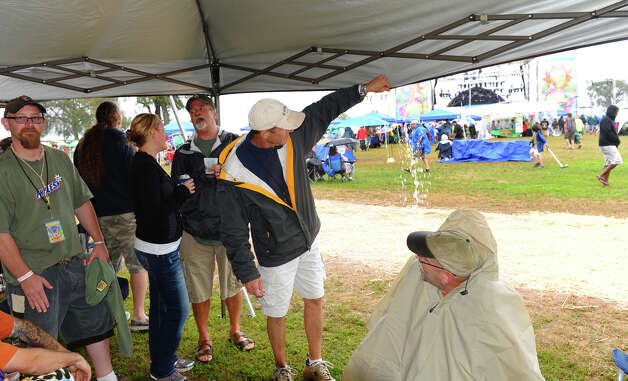 Kevin Hogan, of West Milford, NJ, lets out excess rainwater from the tent while at the Gathering of the Vibes concert at Seaside Park in Bridgeport, Conn. on Friday July 20, 2012. Photo: Christian Abraham / Connecticut Post freelance