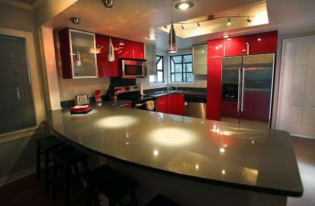Red lacquer cabinetry along with accent lighting in the kitchen, make it stand out.  The home of Eric Geyer on W. Ridgewood.  Thursday, July 19, 2012. (San Antonio Express-News)
