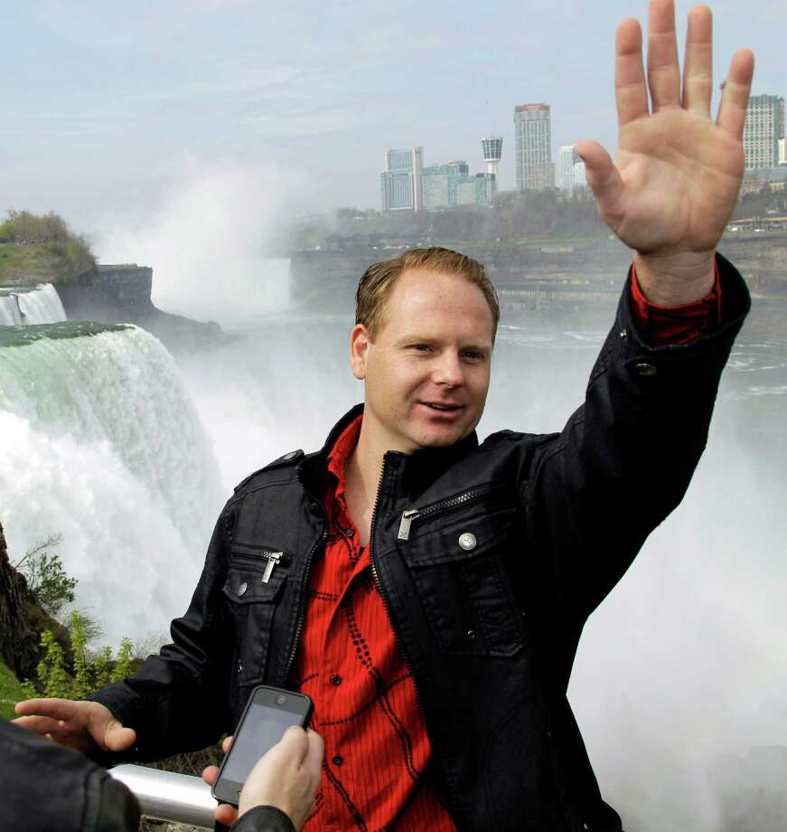 FILE - In this May 2, 2012 file photo, Nik Wallenda waves to tourists after a news conference in Niagara Falls, N.Y. The New York city of Niagara Falls says daredevil Wallenda still owes about $25,000 for public safety costs from last month's tightrope walk across the falls, and it's having a tough time collecting, according to reports Friday, July 20, 2012. Photo: AP