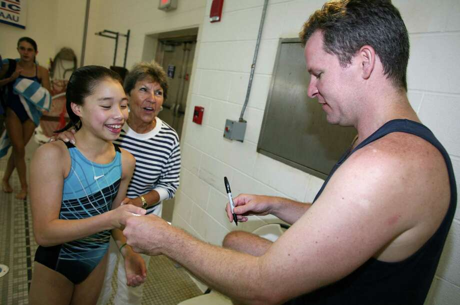 Olympic Silver medalist Scott Donie, right, signs an autograph for Samantha Ho, 11, left, at the conclusion of a two day diving clinic he conducted at the Greenwich YMCA Friday, July, 20, 2012. Photo: David Ames / Greenwich Time
