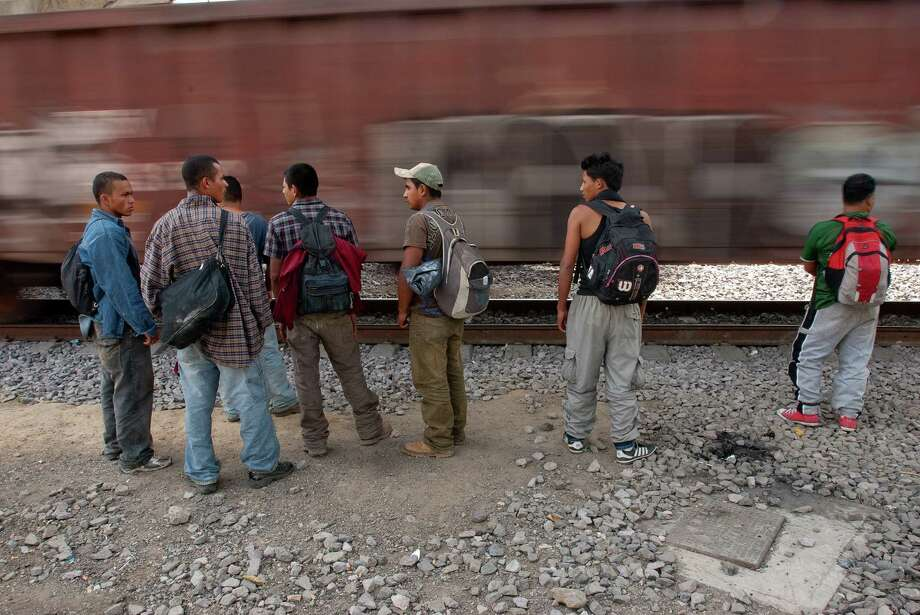 As a northbound freight speeds through the outskirts of Mexico City, Central American migrants weigh their chances of hopping it. Photo: Keith Dannemiller / ©2012 Keith Dannemiller