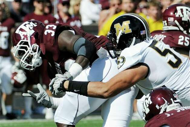 FILE - In this Oct. 16, 2010, file photo, Texas A&M running back Christine Michael (33) tries to gain yardage as Missouri defender Brad Madison (57) reaches for him during the first half of an NCAA college football game in College Station, Texas. Madison had three sacks in the game. (AP Photo/Pat Sullivan, File) Photo: Pat Sullivan, Associated Press