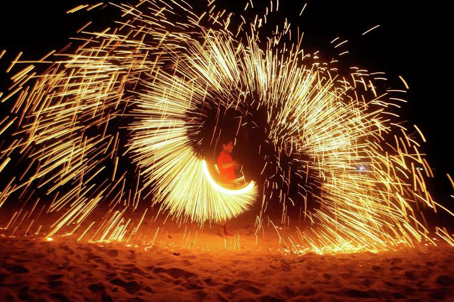 A Palestinian boy plays with fireworks as he celebrates the start of the Muslim holy month of Ramadan in Gaza City, Friday, July 20, 2012. Photo: Hatem Moussa, Associated Press / AP