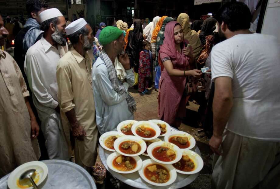 A Pakistani woman gives money to an owner of a restaurant to provide food to poor people as Muslim's fasting month of Ramadan starts, in Rawalpindi, Pakistan on Friday, July 20, 2012. Photo: B.K. Bangash, Associated Press / AP