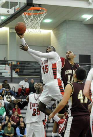Central's #15 Jerome Parkins attempts a layup as Sacred Heart's #10 Josh Turner comes in to block from behind, during Division LL semi-final action in New Haven, Conn. on Tuesday Feb. 03, 2010. Photo: Christian Abraham, ST / http://connpost.com/