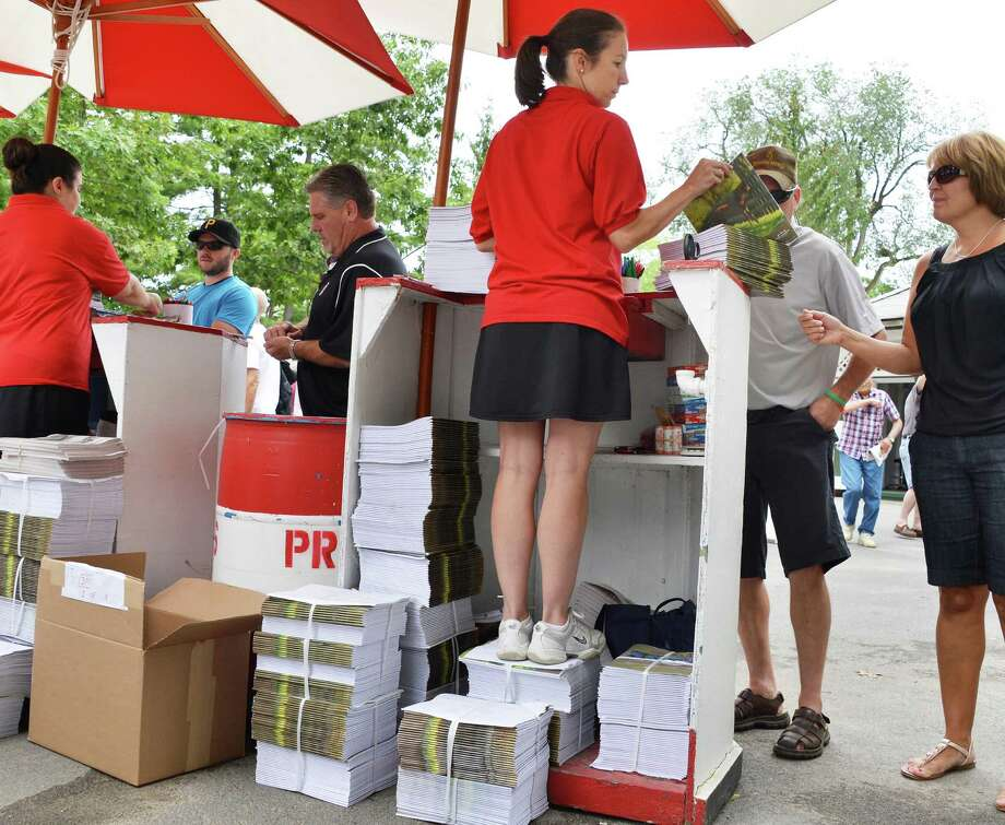 Kelly McKinley of Saratoga Springs stands atop stacks of the racing programs she's selling duringSaratoga Race Course's opening day Friday July 20, 2012.   (John Carl D'Annibale / Times Union) Photo: John Carl D'Annibale / 00018477B